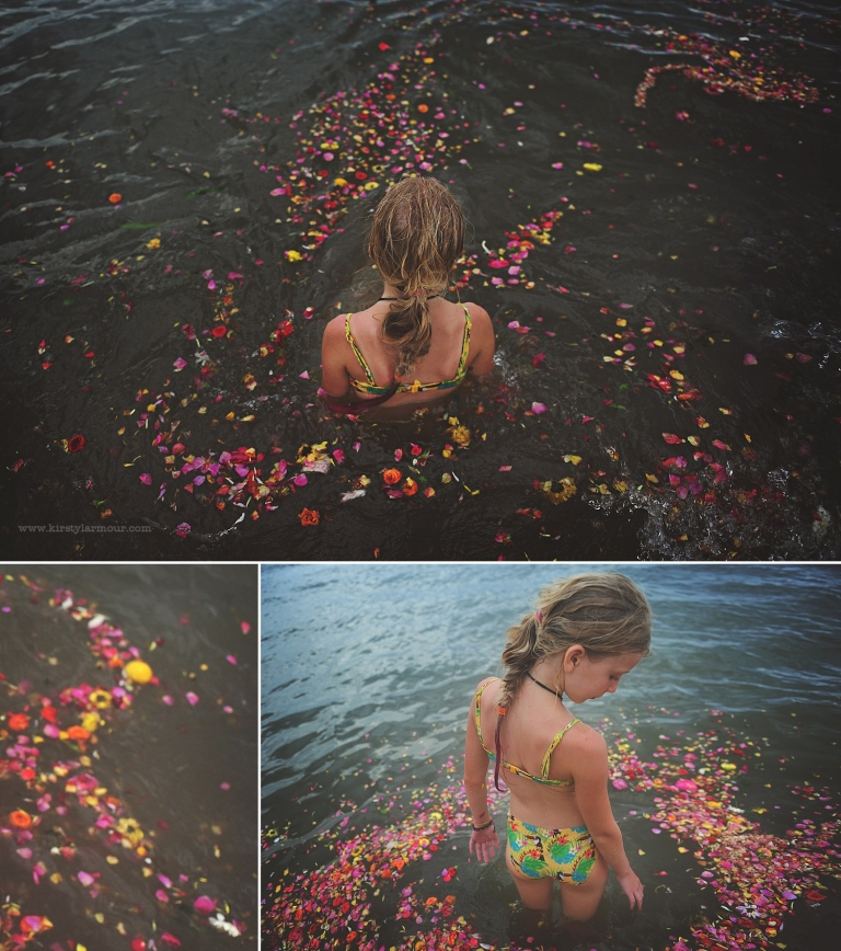 a girl sits in water surrounded by flowers on a beach in Chennai, India, by Kirsty larmour
