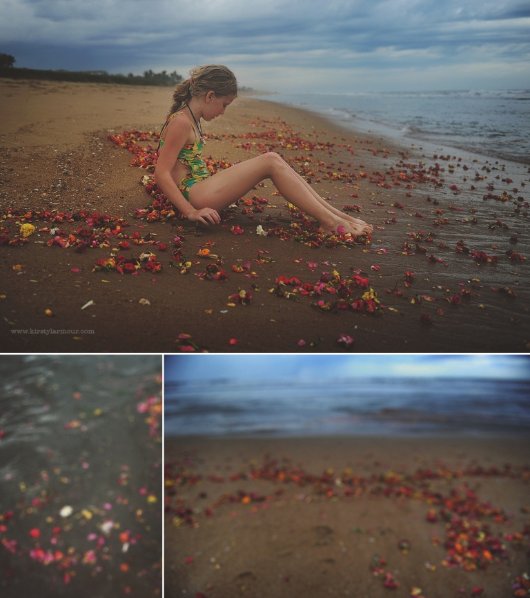 A peaceful scene with a girl sitting amongst flowers on a beach in India by Kirsty Larmour