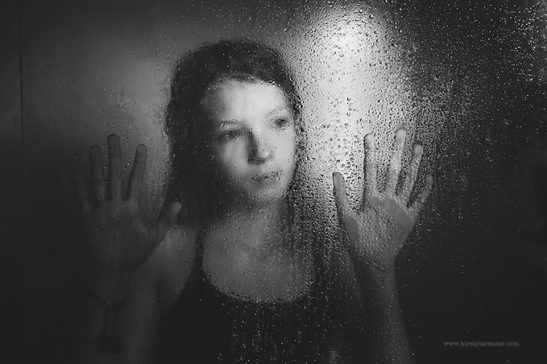 A girl stands behind a blurry, water dropped shower screen